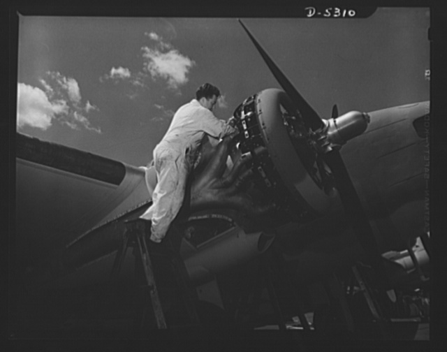 """Production. Aircraft. A mechanic in the flight test group of a large Western aircraft factory checks the power plant of a Lockheed """"Hudson"""" bomber after its initial flight"""
