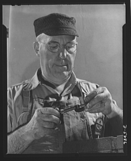 """Production. Aircraft. Although the tiny part in this veteran's """"mike"""" looks insignificant, its variation from perfection may mean a jammed gun, faulty landing gear, or stalled engine. This machinist in a large Western aircraft plant has had twenty-three years of experience. Craftsmen of his skill are at an all-time premium now"""