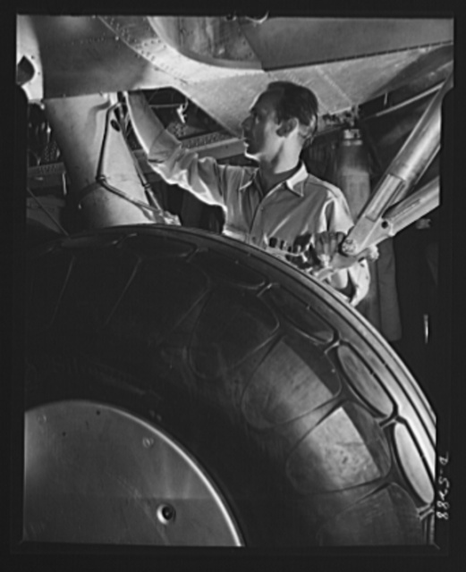 Production. Aircraft. At the end of a Flying Fortress assembly line, this mechanic in a large Western plant makes a final check on a landing gear hydraulic system. That big round object in the foreground is a rubber tire. Remember?