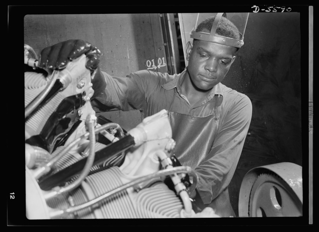 "Production. Aircraft engines. A young Negro worker stands ready to wash or ""degrease"" this airplane motor prior to its shipment. He's an employee of a large Midwest airplane plant. Melrose Park, Buick plant"