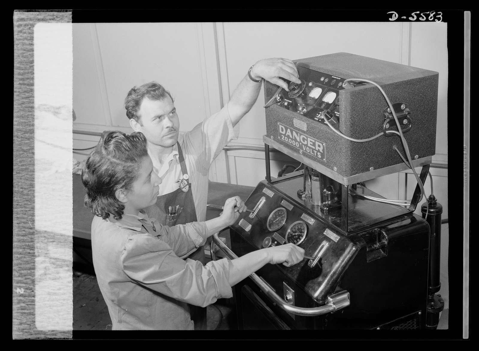 Production. Aircraft engines. Foreman F.I. Bowman shows Marietta Morgan how to operate this bomb-test machine used to test reconditioned spark plugs. A young Negro girl, Marietta, had formerly been a clerk in a meat market. Her lack of industrial experience, however, has been no handicap for her present war job in a large Midwest airplane plant. She's rapidly becoming a skilled and efficient machine operator. Melrose Park, Buick plant