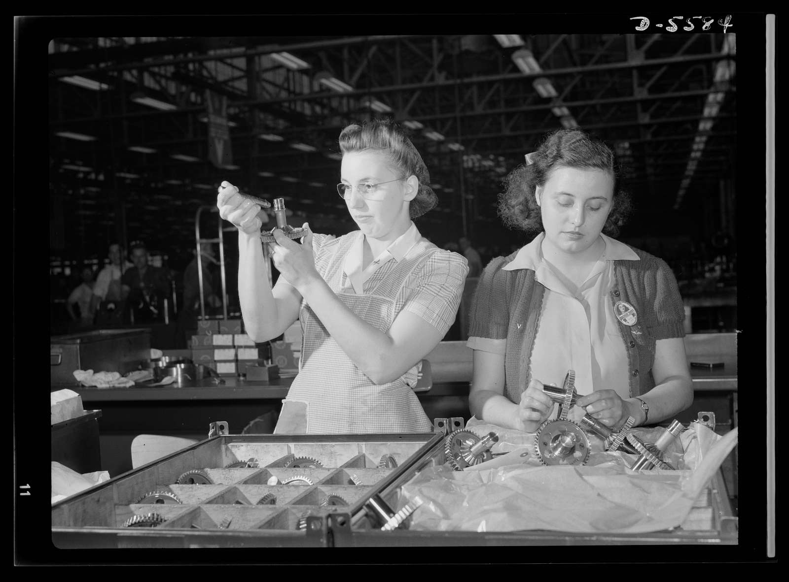 Production. Aircraft engines. Hundreds of gears pass through the expert hands of Dorothy Miller and Sylvia Dreiser during their eight-hour working day in a large Midwest aircraft plant. Inspection of these vital cogs in America's war machine is a delicate task and one which requires infinite patience and precision. Melrose Park, Buick plant