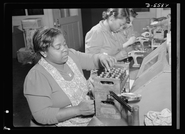 Production. Aircraft engines. Negro women with no previous industrial experience are reconditioning used spark plugs in a large Midwest airplane plant. Despite their lack of technical knowlege, these women have become expert operators of the small testing machines. Melrose Park, Buick plant