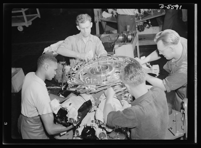 Production. Aircraft engines. Typifying American democracy at work, four soldiers of the production front assemble an airplane engine for Uncle Sam's soldiers of the battlefront. In this, as in other war factories throughout the U.S., prejudice pertaining to differences of race, creed or color have been scrapped by those who recognize that victory must have priority over intolerance. These four men are assembling cylinder barrels to an engine in a giant Midwest aviation plant. Melrose Park, Buick plant