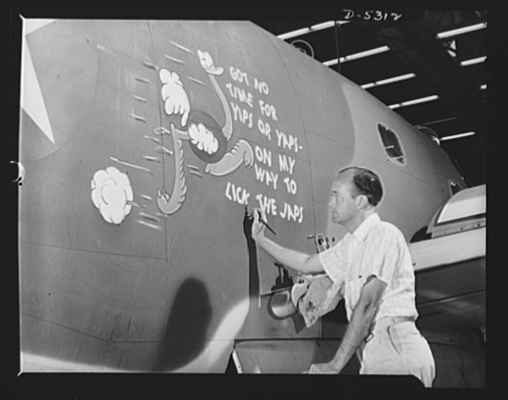 """Production. Aircraft. George """"Randy"""" McCraw decorating a Vega Ventura bomber. Every ship that rolls off the line carries a cartoon aimed at the Axis. George came to work as a spray painter, then shifted to painting British insignia on sides of ships. He sometimes amused his fellow workers by drawing faces on ships during lunch hour, and was prevailed upon to put a big drawing on a ship for a special occasion. The idea took, and now George puts a gag drawing on each ship. The paint washes off with gasoline, but overseas gossip says these ships go into combat still bearing assorted Rudy Ostriches, Donald Ducks, Porky Pigs and a host of other cartoon characters"""