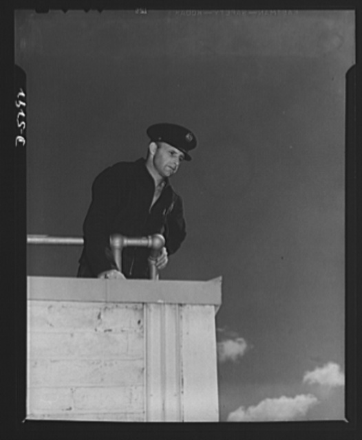Production. Aircraft. High above the roof of a Western aircraft plant covering nearly two million square feet of shop and assembly space, this fireman keeps a watchful eye on the scene below. During an air raid his post is here, as a spotter for the incendiary's flare