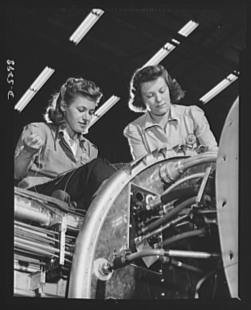 Production. Aircraft. High on the wing of a Vega Ventura bomber, these girl electricians complete a complicated wiring assembly