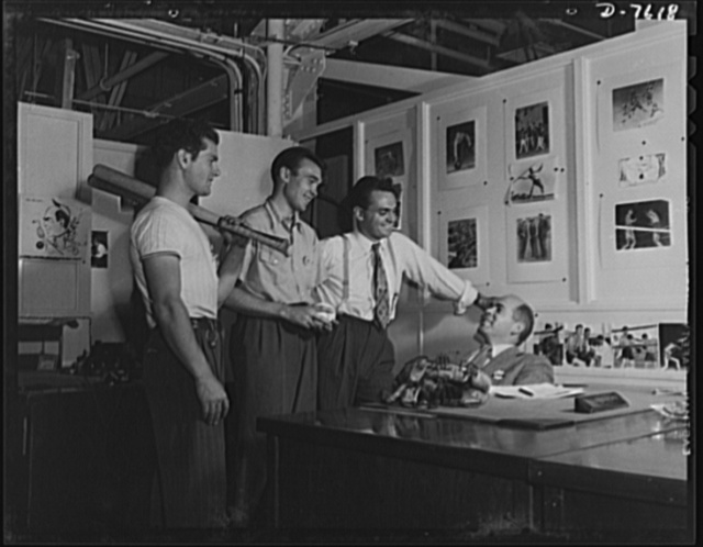 """Production. Airplane manufacture, general. A group of employees at the Inglewood, California, plant of North American Aviation, discuss the evening inter-department softball game with Ken Kellough, recreation director. The recreation department sponsors softball, baseball, basketball, tennis, swimming, boxing, golf, track, bowling, ice hockey, a rifle club, horseback riding club, and a ski club. Trophies are given to winning teams in inter-department competiton. This plant produces the battle-tested B-25 (""""Billy Mitchell) bomber, used in General Doolittle's raid on Tokyo, and the P-51 (""""Mustang"""") fighter plane which was first brought into prominence by the British raid on Dieppe"""