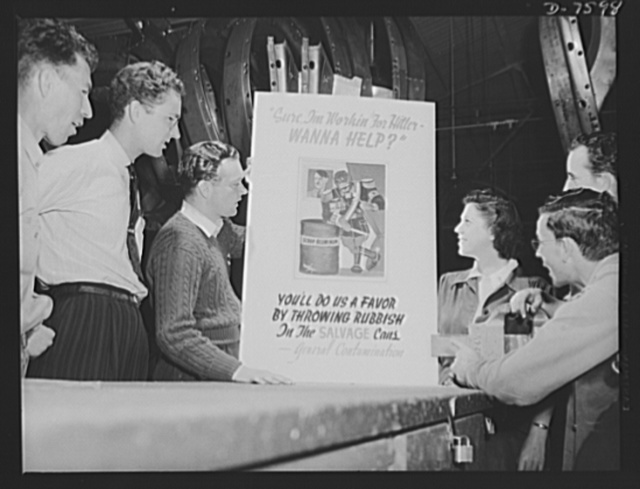 """Production. Airplane manufacture, general. A group of North American employees at Inglewood, California, look over a new poster on material conservation. The department which produced the poster is saving tons of vital material. This plant produces the battle-tested B-25 (""""Billy Mitchell"""") bomber, used in General Doolittle's raid on Tokyo, and the P-51 (""""Mustang"""") fighter plane, which was first brought into prominence by the British raid on Dieppe"""