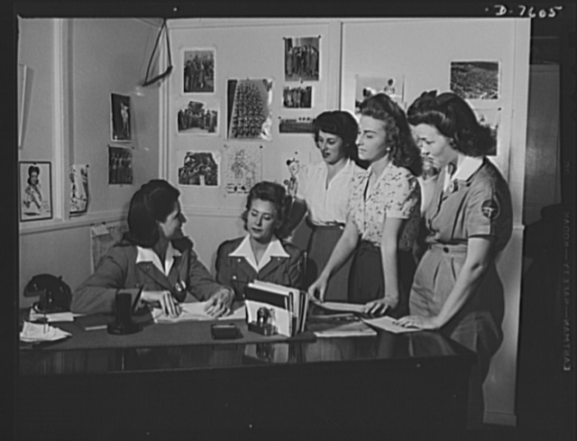 """Production. Airplane manufacture, general. A group of North American's  women employees at Inglewood, California, discuss a coming sports event with Bonnie Edlund, women's activities director. This plant produces the battle-tested B-25 (""""Billy Mitchell"""") bomber, used in General Doolittle's raid on Tokyo, and the P-51 (""""Mustang"""") fighter plane, which was first brought into prominence by the British raid on Dieppe"""