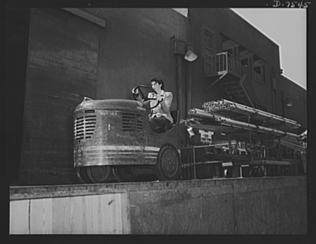 "Production. Airplane manufacture, general. A woman employee in the dispatching department at the Inglewood, California, plant of North American Aviation, Incorporated, hauls another load of vital materials to the proper department. This plant produces the battle-tested (""Billy Mitchell"") bomber, used in General Doolittle's raid on Tokyo, and the P-51 (""Mustang"") fighter plane, which was first brought into prominence by the British raid on Dieppe"