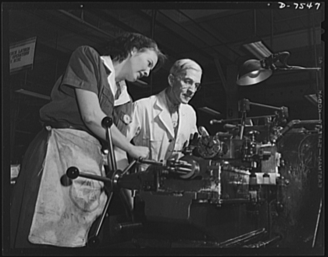 "Production. Airplane manufacture, general. A woman employee operates a turret lathe under close supervision of a skilled machinist in a modern machine shop at the Inglewood, California, plant of North American Aviation, Incorporated. This plant produces the battle-tested (""Billy Mitchell"") bomber, used in General Doolittle's raid on Tokyo, and the P-51 (""Mustang"") fighter plane, which was first brought into prominence by the British raid on Dieppe"