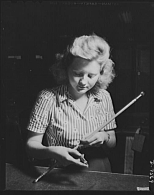 """Production. Airplane manufacture, general. A woman inspector at North American's Inglewood, California, plant uses a micro-meter in testing control rods to be used in bomber and fighter planes. This plant produces the battle-tested B-25 (""""Billy Mitchell"""") bomber, used in General Doolittle's raid on Tokyo, and the P-51 (""""Mustang"""") fighter plane, which was first brought into prominence by the British raid on Dieppe"""