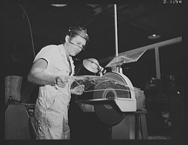 """Production. Airplane manufacture, general. After lucite (a shatter-proof plastic """"glass"""") is formed for transparent enclosures, the edges are cut to the right size on an enemy wheel at the North American Aviation plant at Inglewood, California. This plant produces the battle-tested B-25 (""""Billy Mitchell"""") bomber, used in General Doolittle's raid on Tokyo, and the P-51 (""""Mustang"""") fighter plane, which was first brought into prominence by the British raid on Dieppe"""