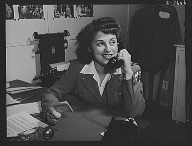 """Production. Airplane manufacture, general. Dolores Cook of North American's welfare department  at Inglewood, California, makes an appointment for an employee to have his driver's license revised. She wears the uniform of the company's Red Cross unit. This plant produces the battle-tested B-25 (""""Billy Mitchell"""") bomber, used in General Doolittle's raid on Tokyo, and the P-51 (""""Mustang"""") fighter plane, which was first brought into prominence by the British raid on Dieppe"""