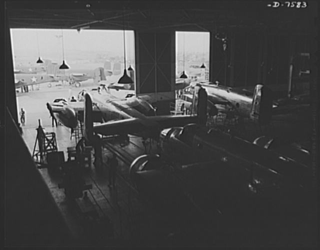 """Production. Airplane manufacture, general. Looking out the door at the end of North American's B-25 final assembly line at Inglewood, California. This plant produces the battle-tested B-25 (""""Billy Mitchell"""") bomber, used in General Doolittle's raid on Tokyo, and the P-51 (""""Mustang"""") fighter plane, which was first brought into prominence by the British raid on Dieppe"""