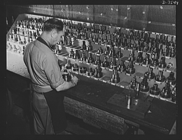 """Production. Airplane manufacture, general. Punch-press dies are kept in order by this North American Aviation employee, who delivers them to the proper machines for specific jobs at the Inglewood, California, plant. This plant produces the battle-tested (""""Billy Mitchell"""") bomber, used in General Doolittle's raid on Tokyo, and the P-51 (""""Mustang"""") fighter plane, which was first brought into prominence by the British raid on Dieppe"""