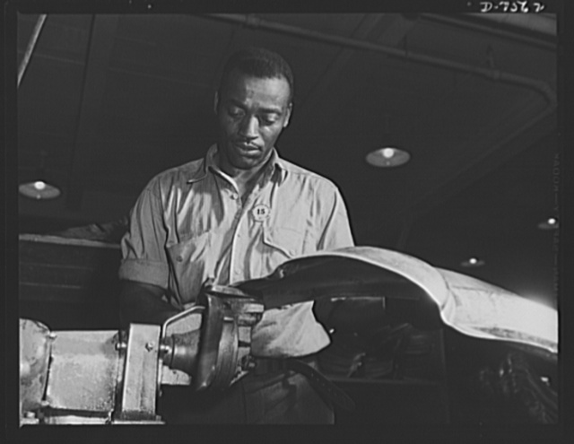 """Production. Airplane manufacture, general. This Negro employee runs a shear in the sheet metal department of North American's Inglewood, California, plant. Sheet metal plane parts are trimmed to the correct size by the use of a high speed electric shear. This plant produces the battle-tested B-25 (""""Billy Mitchell"""") bomber, used in General Doolittle's raid on Tokyo, and the P-51 (""""Mustang"""") fighter plane, which was first brought into prominence by the British raid on Dieppe"""