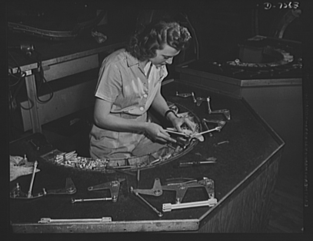 "Production. Airplane manufacture, general. This woman employee at North American's Inglewood, California, plant, assembles control brackets for bomber and fighter planes. All parts are arranged conveniently in the semi-circle. This plant produces the battle-tested B-25 (""Billy Mitchell"") bomber, used in General Doolittle's raid on Tokyo, and the P-51 (""Mustang"") fighter plane, which was first brought into prominence by the British raid on Dieppe"