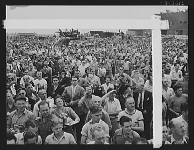 """Production. Airplane manufacture, general. Thousands of North American Aviation employees at Inglewood, California look skyward as the bomber and fighter planes they helped build perform overhead during a lunch period air show. This plant produces the battle-tested (""""Billy Mitchell"""") bomber, used in General Doolittle's raid on Tokyo, and the P-51 (""""Mustang"""") fighter plane, which was first brought into prominence by the British raid on Dieppe"""