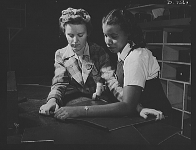 """Production. Airplane manufacture, general. Two women employees work together with power shears at the Inglewood, California, plant of North American Aviation, Incorporated. They are cutting sheet metal sections that will be formed into parts for bomber and fighter planes. This plant produces the battle-tested B-25 (""""Billy Mitchell"""") bomber, used in General Doolittle's raid on Tokyo, and the P-51 (""""Mustang"""") fighter plane, which was first brought into prominence by the British raid on Dieppe"""