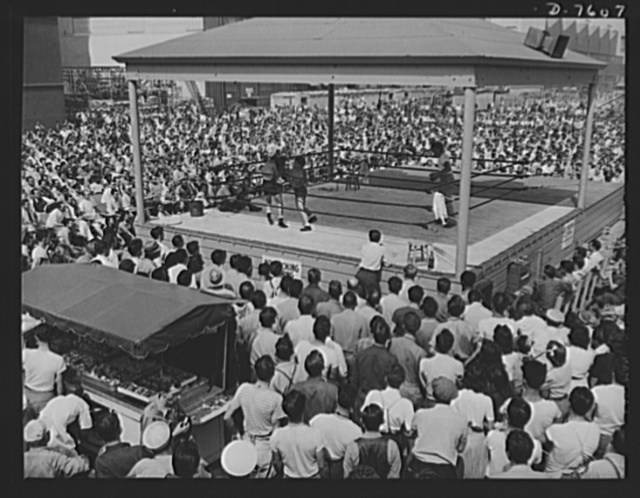 """Production. Airplane manufacture, general. Varied programs are presented at North American's Inglewood, California, plant during lunch period. Here thousands watch a boxing match between two employees. This plant produces the battle-tested B-25 (""""Billy Mitchell"""") bomber, used in General Doolittle's raid on Tokyo, and the P-51 (""""Mustang"""") fighter plane, which was first brought into prominence by the British raid on Dieppe"""