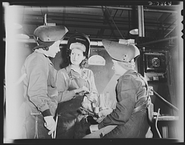 "Production. Airplane manufacture, general. Women arc welders discuss the production of motor mounts and welded parts in a welding booth at the  Inglewood, California, plant of North American Aviation, Incorporated. This plant produces the battle-tested B-25 (""Billy Mitchell"") bomber, used in General Doolittle's raid on Tokyo, and the P-51 (""Mustang"") fighter plane, which was first brought into prominence by the British raid on Dieppe"