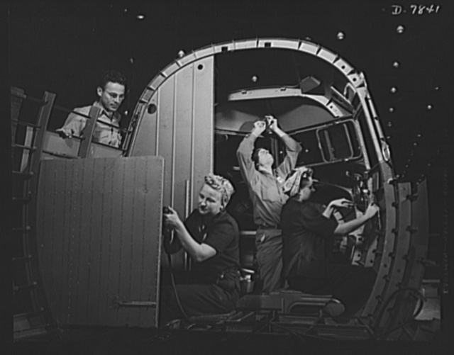 "Production. Airplane maufacture, general. Experienced men help women trainees to learn the intricacies of modern airplane construction at the Long Beach, California, plant of Douglas Aircraft Company. Most important of the many types of aircraft made at this plant are the B-17F (""Flying Fortress"") heavy bomber, the A-20 (""Havoc"") assault bomber and the C-47 heavy transport plane for the carrying of troops and cargo"