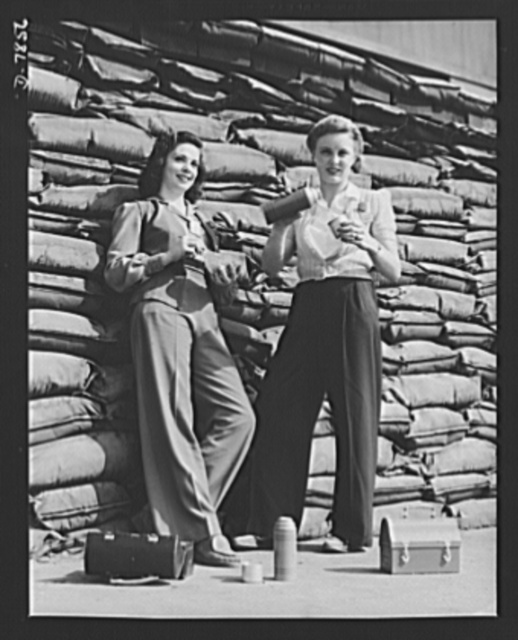 "Production. Airplane maufacture, general. Lunchtime brings a few minutes of rest for these women workers of the assembly line at Douglas Aircraft Company's Long Beach, California, plant. Sand bags for protection against air raids form the background. Most important are the many types of aircraft made at this plant are the B-17F (""Flying Fortress"") heavy bomber, the A-20 (""Havoc"") assault bomber and the C-47 heavy transport plane for the carrying of troops and cargo"