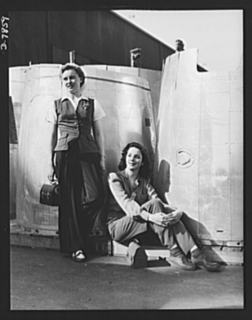 "Production. Airplane maufacture, general. Two assembly line worker at the Long Beach, California, plant of Douglas Aircraft Company, enjoy a well-earned lunch period. Nacelle parts for a heavy bomber form the background. Most important are the many types of aircraft made at this plant are the B-17F (""Flying Fortress"") heavy bomber, the A-20 (""Havoc"") assault bomber and the C-47 heavy transport plane for the carrying of troops and cargo"
