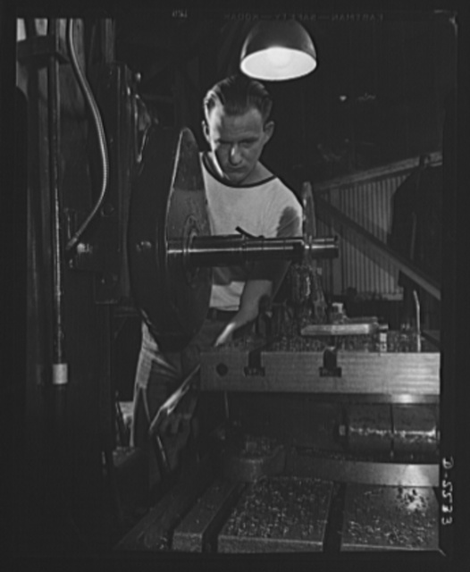 Production. Airplanes. A machinist's apprentice on a Universal boring machine in a big Western airplane plant. Cutting a part for a manufacturing jig with a twelve inch milling cutter