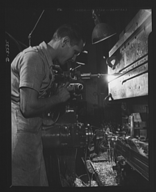 Production. Airplanes. A toolmaker's apprentice at work on a Pratt and Whitney automatic tool room machine in a large Western aircraft plant. He is working on a flap track for a Lockheed Model 58