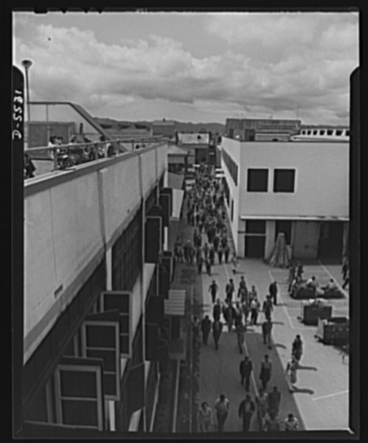 """Production. Airplanes. """"Main Street"""" of a huge Western aircraft plant during the lunch period. At left, girls enjoy lunch on a sun deck"""