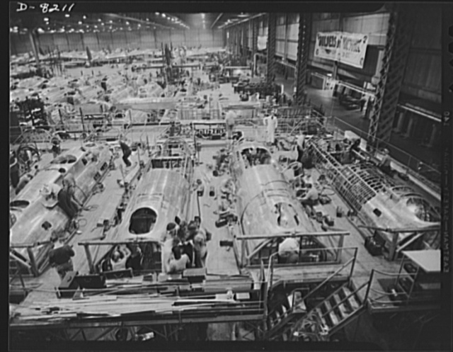 "Production. B-17 heavy bomber. Fast, expert workers at the Boeing plant in Seattle apply outer ""skins"" to fuselage sections for new B-17F (Flying Fortress) bombers, while assembly and fitting operations go forward in the interiors. The Flying Fortress has performed with great credit in the South Pacific, over Germany and elsewhere. It is a four-engine heavy bomber capable of flying at high altitudes"