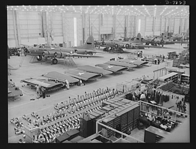 """Production. B-17F heavy bombers. A tidy final assembly line at the Long Beach, California, plant of Douglas Aircraft Company, sends B-17F heavy bombers to the flight lines at a rapid rate. Better known as the """"Flying Fortress,"""" the B-17F is a later model of the B-17, which distinguished itself in action in the South Pacific, over Germany and elsewhere. It is a long range, high altitude, heavy bomber with a crew of seven to nine men and with armament sufficient to defend itself on daylight missions"""