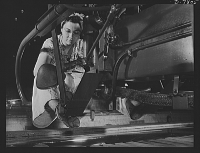 "Production. B-17F heavy bombers. A woman worker at the Long Beach, California, plant of Douglas Aircraft Company, spot welds wing skin sheets for a B-17F heavy bomber. The welding machine is suspended over sheets which move on a platform below her. Better known as the ""Flying Fortress,"" the B-17F is a later model of the B-17, which distinguished itself in action in the South Pacific, over Germany and elsewhere. It is a long range, high altitude, heavy bomber, with a crew of seven to nine men and with armament sufficient to defend itself on daylight missions"