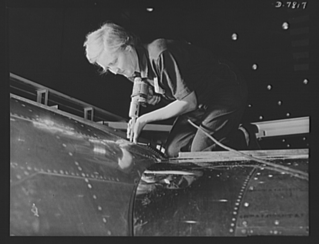 """Production. B-17F heavy bombers. A women worker, over 60 years old, does an expert riveting job on a B-17F bomber in the Long Beach, California, plant of Douglas Aircraft Company. Better known as the """"Flying Fortress,"""" the B-17F is a later model of the B-17, which distinguished itself in action in the South Pacific, over Germany and elsewhere. It is a long range, high altitude, heavy bomber with a crew of seven to nine men and with armament sufficient to defend itself on daylight missions"""
