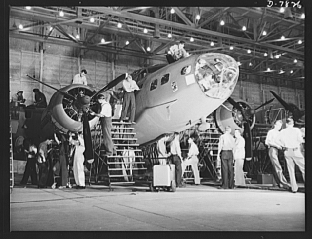 """Production. B-17F heavy bombers. Busy workers at the Long Beach, California, plant of Douglas Aircraft Company, groom a new B-17F heavy bomber as the """"Flying Fortress."""" The B-17F is a later model of the B-17, which distinguished itself in action in the South Pacific, over Germany and elsewhere. It is a long range, high altitude, heavy bomber with a crew of seven to nine men and with armament sufficient to defend itself on daylight missions"""