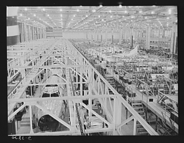 """Production. B-17F heavy bombers. Overall view of a conveyor assembly line at the Long Beach, California, plant of Douglas Aircraft Company, showing B-17F fuselages going through and, at right, sectional fuselage jigs in which fuselage halves are assembled from prefabricated parts. Better known as the """"Flying Fortress,"""" the B-17F is a later model B-17, which distinguished itself in action in the South Pacific, over Germany and elsewhere. It is a long range, high altitude, heavy bomber with a crew of seven to nine men and with armament sufficient to defend itself on daylight missions"""