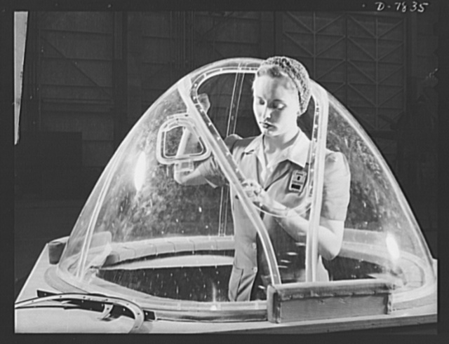 "Production. B-17F heavy bombers. This girl in a glass house is putting finishing touches on the bombardier nose section of a B-17F heavy bomber. She's one of many capable women workers in the Long Beach, California, plant of the Douglas Aircraft Company. Better known as the ""Flying Fortress,"" the B-17F is a later model B-17, which distinguished itself in action in the South Pacific, over Germany and elsewhere. It is a long range, high altitude, heavy bomber with a crew of seven to nine men with armament sufficient to defend itself on daylight missions"