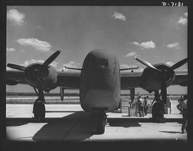 Production. B-24 bombers and C-87 transports. A new consolidated transport, just off the assembly line of a Western aircraft plant are loaded with cargo. The site of the plant and flying field was a cow pasture not so long before Pearl Harbor. This new transport, an adaptation of the B-24 bomber, is known as the C-87 and carries one of the greatest human or cargo loads of any plane now in mass production. It is built in a plant equipped with one of the best and most modern air conditioning and fluorescent lighting systems in the country