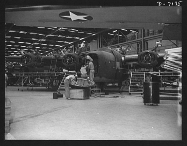 "Production. B-24 bombers and C-87 transports. Another mighty warship of the air will soon be ready for ""launching."" A nose door is being readied for assembly on a new consolidated transport plane at the end of the assembly line of a western aircraft plant. This new transport, an adaptation of the B-24 bomber, is known as the C-87 and carries one of the greatest human or cargo loads of any plane now in mass production. It is built in a plant equipped with one of the best air conditioning"