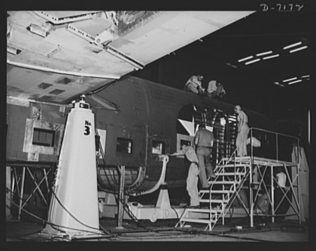 Production. B-24 bombers and C-87 transports. Final additions are made to the shell of a consolidated transport plane in preparation for its trip down the final assembly line of a Western aircraft plant. This new transport, an adaptation of the B-24 bomber, is known as the C-87, and carries one of the greatest human or cargo loads of any plane now in mass production. It is built in a plant equipped with one of the best air conditioning and fluorescent lighting systems in the country