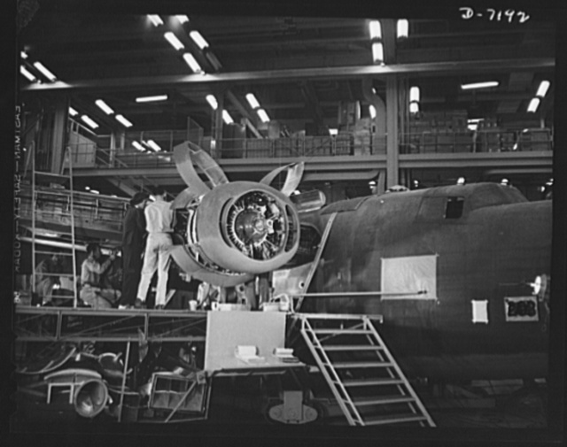 Production. B-24 bombers and C-87 transports. Installing one of the four engines of a mighty consolidated transport plane at a Western aircraft plant. This new transport, an adaptation of the B-24, which is known as the C-87, and carries one of the greatest human or cargo loads of any plane now in mass production. It is built in a plant equipped with one of the best and most modern air conditioning and fluorescent lighting systems in the country