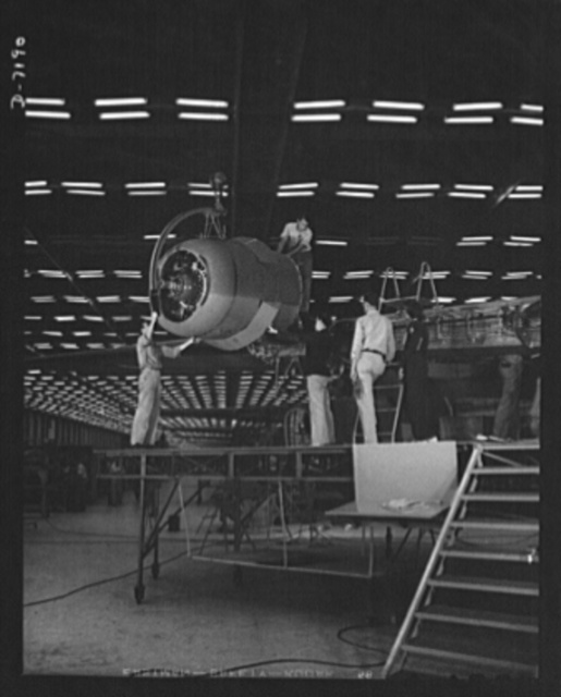 Production. B-24 bombers and C-87 transports. Lowering one of the four engines of a mighty consolidated transport plane at a Western aircraft plant. This new transport, an adaptation of the B-24, which is known as the C-87, and carries one of the greatest human or cargo loads of any plane now in mass production. It is built in a plant equipped with one of the best and most modern air conditioning and fluorescent lighting systems in the country