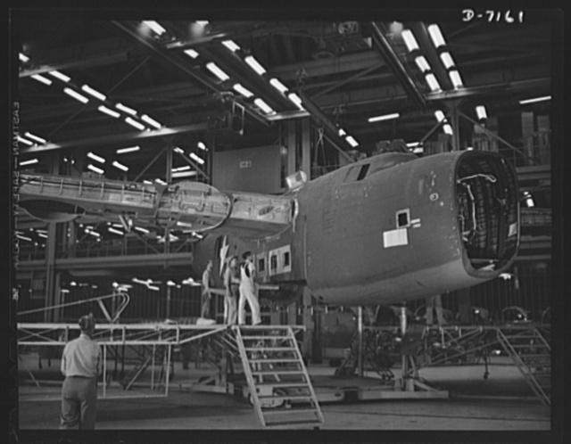 Production. B-24 bombers and C-87 transports. Mated fuselage, nose and wing center sections of a consolidated transport plane are lowered as a unit into the carriage on which the shell will travel along the final assembly line. This new transport, an adaptation of the B-24 bomber, is known as the C-87, and carries one of the greatest human or cargo loads of any plane now in mass production. It is built in a plant equipped with the best and most modern air conditioning and fluorescent lighting systems in the country