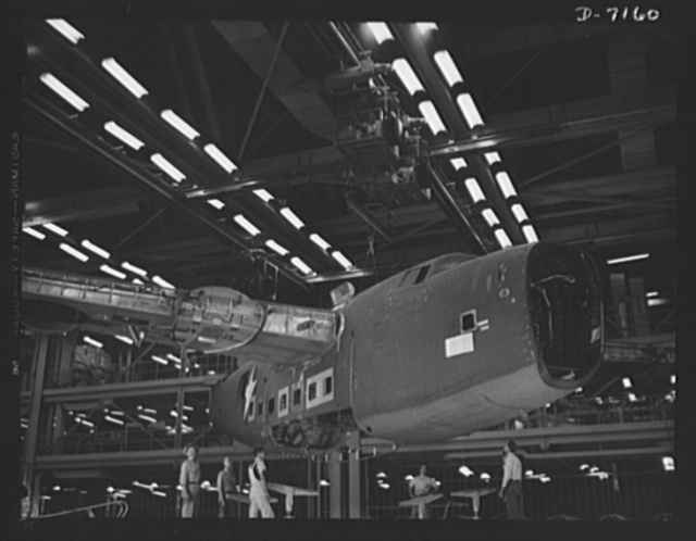 Production. B-24 bombers and C-87 transports. Mated sections of a consolidated transport plane are lifted by a monorail crane from a fuselage mating fixture of a Western aircraft plant.  It will next be deposited in a carriage which will carry it along the assembly line. This new transport, an adaptation of the B-24 bomber, is known as the C-87, and carries one of the greatest human or cargo loads of any plane now in mass production. It is built in a plant equipped with the best and most modern air conditioning and fluorescent lighting systems in the country