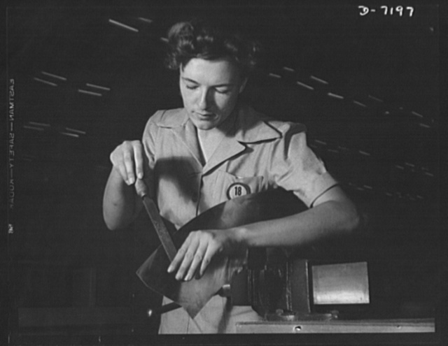 Production. B-24 bombers and C-87 transports. Nell Roy Johnson at her first job. She is filing burrs from parts to be used in making consolidated transport planes at a Western plant. This transport ship is adapted from the B-24 bomber, and carries one of the greatest human or cargo loads of any plane now in mass production.