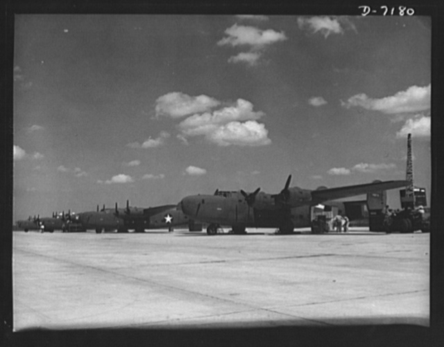 Production. B-24 bombers and C-87 transports. New consolidated transport, just off the assembly line of a Western aircraft plant are loaded with cargo. The site of the plant and flying field was a cow pasture not so long before Pearl Harbor. This new transport, an adaptation of the B-24 bomber, is known as the C-87 and carries one of the greatest human or cargo loads of any plane now in mass production. It is built in a plant equipped with one of the best and most modern air conditioning and fluorescent lighting systems in the country