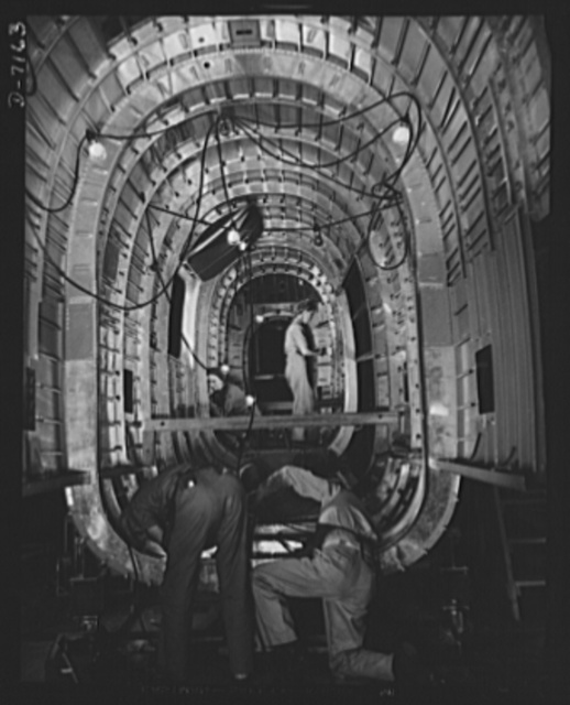 "Production. B-24 bombers and C-87 transports. Structural parts of a consolidated transport plane are installed in the ""tunnel"" of a tail fuselage section in a Western aircraft plant. This new transport, an adaptation of the B-24 bomber, is known as C-87, and carries one of the greatest human or cargo loads of any plane now in mass production. It is built in a plant equipped with the best and most modern air conditioning and fluorescent lighting systems"